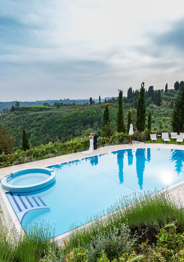 couple admiring the panorama from the swimming pool of a Tuscan Villa