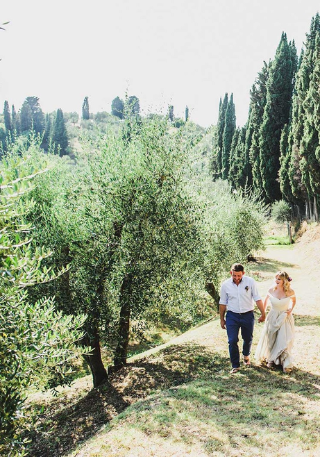 couple walking through the olive trees Tuscany